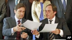 Pedro Passos Coelho (L), leader of Social Democrat Party (PSD) and Paulo Portas, leader of Popular Party, exchange their coalition agreement documents for the government in Lisbon, Portugal, June 16, 2011