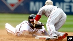 Jason Heyward of Atlanta, left, tries to touch the base before being tagged out by Dustin Pedroia at a baseball game on May 26, 2014.