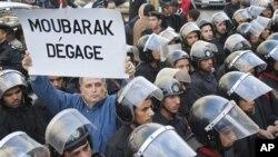 """在開羅﹐一名示威者在警察叢中舉起""""穆巴拉克下臺""""的標語牌"""