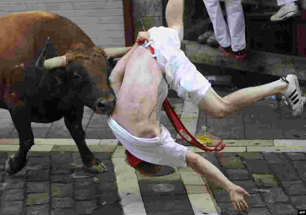 "A Jandilla bull charges at a participant during the first ""encierro"" (bull-run) of the San Fermin Festival in Pamplona, northern Spain."