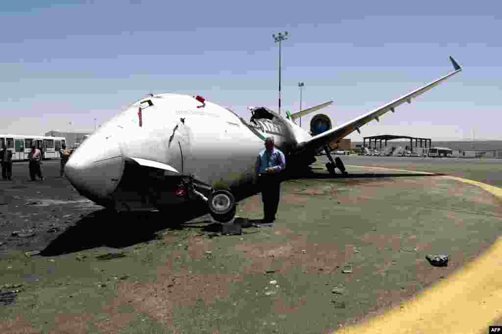 A Yemeni airport official looks at a destroyed Felix Airways plane, after it was hit in an air strike, at the international airport of Yemen's capital, Sana'a.