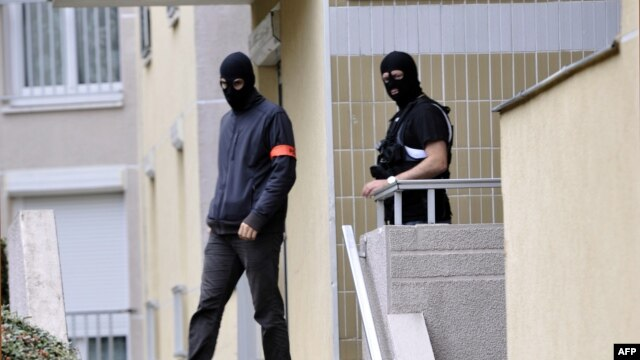 Policemen leave an appartment building, where investigators searched a lock-up garage possibly used by people arrested during an anti-terror operation conducted four days ago, October 10, 2012 in Torcy, east of Paris.