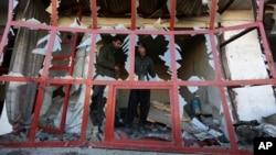 Seorang penjaga toko mengamati suasana di sekitarnya dari jendela tokonya yang hancur akibat serangan bom bunuh diri di Kabul, Afghanistan (28/12).