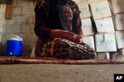 FILE - A 15-year-old Yazidi girl who had been captured by the Islamic State group and forcibly married to a militant in Syria, but later escaped, sits on the floor of her family's house during an interview in Maqluba, Iraq, Oct. 8, 2014.