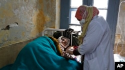 FILE - An elderly Kashmiri tuberculosis patient receives treatment at the Chest Disease Hospital on World Tuberculosis Day in Srinagar, India, March 24, 2015.