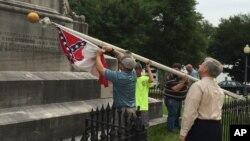 Para pekerja menurunkan bendera Konfederasi dari halaman gedung parlemen Alabama di ibukota Montgomery (24/6). (AP/Martin Swant)