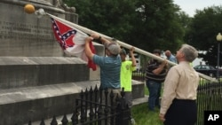 Alabama state workers take down a Confederate flag on the grounds of the state capitol in Montgomery, June 24, 2015.