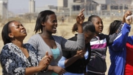 Women from a group of churchgoers  wail at the site, Sunday Aug. 19, 2012 at the Lonmin platinum mine, background, near Rustenburg, South Africa, during a memorial service for 34 dead striking miners who were shot and killed by police last Thursday.