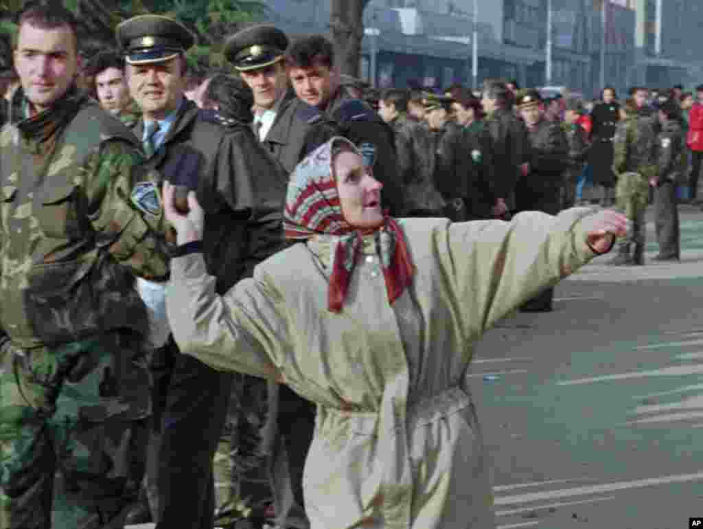 A woman from the eastern Bosnian enclave of Srebrenica throws a rock at the building where the Tuzla region officials are based, while policemen look on. (File 2006)
