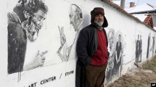 Nikolay, resident of the Staro Zhelezare village poses in front of  a mural depicting his own portrait next to Pope Francis  in the Bulgarian village of Staro Zhelezare, Jan. 27, 2016.