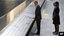 President Barack Obama touches the names of victims engraved on the side of the north pool of the World Trade Center site as former President George W. Bush, first lady Michelle Obama and former first lady Laura Bush (obscured) look on during ceremonies m