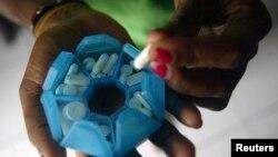 Seorang perempuan yang terinfeksi HIV menyiapkan obat-obat di sebuah rumah penampungan di Jayapura, Provinsi Papua, 27 November 2008.
