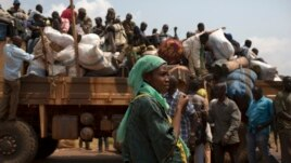 FILE - A woman looks on as people on a truck gather their belongings during a road repatriation to Chad in the capital  Bangui, January 22, 2014.