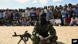 A member of Somalia's al-Shabab militant group sits during a public demonstration to announce integration with al Qaeda, Elasha, south of Mogadishu, February 13, 2012