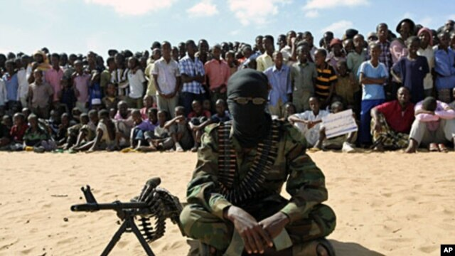 A member of Somalia's al-Shabab militant group sits during a public demonstration to announce integration with al Qaeda, Elasha, south of Mogadishu, February 13, 2012