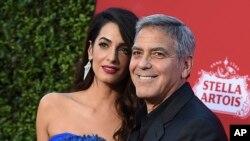 """En esta foto de archivo del 22 de octubre de 2017, Amal Clooney y George Clooney llegan al estreno de """"Suburbicon"""" en Los Ángeles. George y Amal Clooney están donando $ 500,000 a estudiantes que organizan marchas a nivel nacional contra la violencia con armas de fuego, y dicen que también asistirán a las protestas planeadas el próximo mes."""