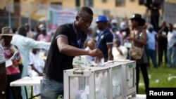 FILE - A party delegate casts his vote during the All Progressives Congress (APC) primary election to choose a governorship candidate for Nigeria's Lagos state, at Onikan stadium in Lagos, Dec. 4, 2014.