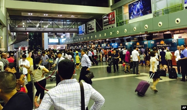Passengers crowd check-in counters at Noi Bai Airport in Hanoi, Vietnam, July 29, 2016.