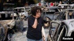 Жінка намагається знайти свою собаку після лісової пожежі в селі Маті, поблизу Афін, Греція. 24 липня 2018 року.