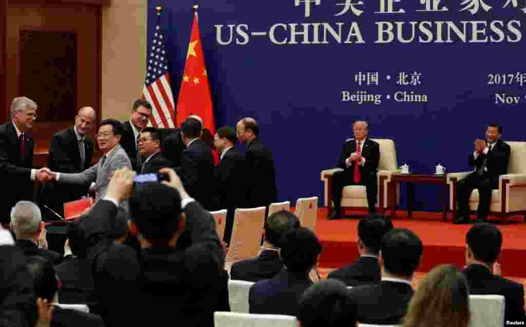 """在北京人民大会堂举行的签约仪式上,美中企业家握手,美国总统川普和中国国家主席习近平参加(2017年11月9日)。川普总统11月13日在马尼拉说:""""我们和贸易伙伴取得了一些重大进展,其幅度超出你的想象。商业公司还做了3000亿美元的生意,包括中国的2500亿美元购买,还会有更多。贸易有很大进展。我们与几乎所有国家都有贸易赤字。这些赤字将很快、很大幅度的缩减。"""""""