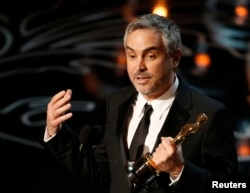 "FILE - Alfonso Cuaron accepts the Oscar for best director for ""Gravity"" at the 86th Academy Awards in Hollywood, California, March 2, 2014."