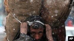 រូបឯកសារ៖ បុរសរស់នៅតំបន់កាស្មៀម្នាក់លីបាវធ្យូង ខណៈពេលមានព្រិលធ្លាក់នៅក្រុង Srinagar ក្នុងតំបន់កាស្មៀគ្រប់គ្រងដោយឥណ្ឌា កាលពីថ្ងៃទី១២ ខែមករា ឆ្នាំ២០២០។