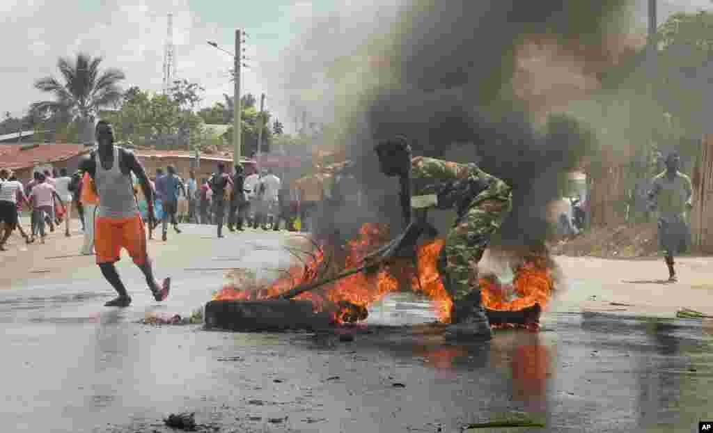 Un soldat de l'armée burundaise tente d'éteindre le feu d'un pneu brulé par les manifestants dans la capitale Bujumbura, Burundi, lundi 27 avril 2015.