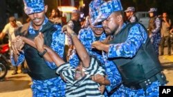Maldivian police officers detain an opposition protester demanding the release of political prisoners during a protest in Male, Maldives, Feb. 2, 2018. Opponents of the Maldives government clashed with police on the streets of the capital Friday as they demanded the release of imprisoned politicians whose convictions were overturned by the Supreme Court.