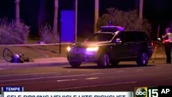 FILE - A still image taken from video provided by ABC-15, shows investigators at the scene of a fatal accident involving a self-driving Uber car on the street in Tempe, Arizona, March 19, 2018.