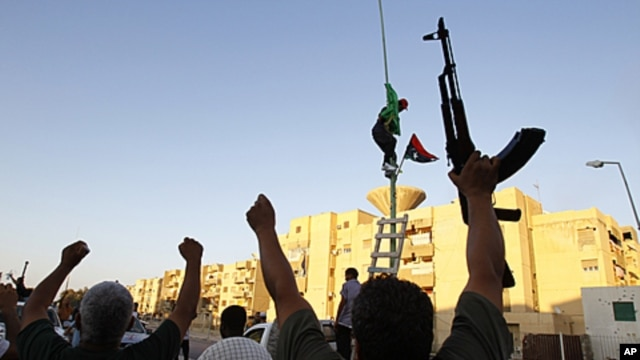 Libyan rebels gesture as they change the flag in Abu Salim district in Tripoli, Libya, August 25, 2011