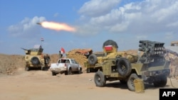 FILE - Iraqi government forces and allied militias fire weaponry from a position in the northern part of Diyala province as they conduct an assault to retake the city of Tikrit from the Islamic State group March 2, 2015. On Monday they launched a similiar assault on Fallujah.