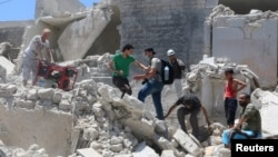 People walk on the rubble of a site hit by a barrel bomb in the rebel-held area of Old Aleppo, Syria, July 11, 2016.