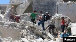 Người dân đi trên đống đổ nát tại nơi bị trúng một quả bom thùng trong khu vực do phiến quân kiểm soát Old Aleppo, Syria, ngày 11 tháng 7 năm 2016.