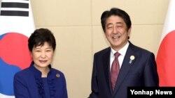 박근혜 한국 대통령(왼쪽)과 아베 신조 일본 총리가 7일 라오스 비엔티안 국립컨벤션센터(NCC)에서 열린 정상회담에서 악수하고 있다.