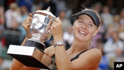 Maria Sharapova of Russia holds the trophy after winning the women's final match against Sara Errani of Italy at the French Open tennis tournament in Roland Garros stadium in Paris, June 9, 2012.