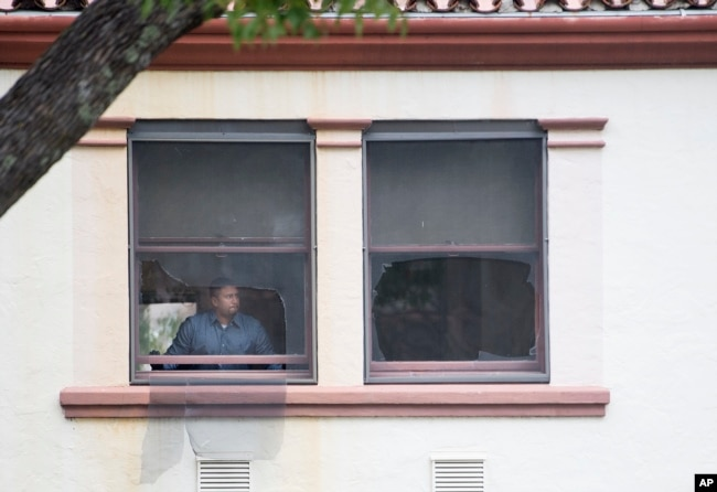 A man adjusts a damaged window at the location where a hostage situation with an active shooter ended tragically at the Veterans Home of California in Yountville, Calif., March 10, 2018.