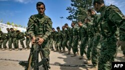 Borci Sirijskih demokratskih snaga (SDF), koje predvode Kurdi a podržava Amerika, u blizini naftnog polja Omar u istočnoj Siriji, igraju nakon proglašenja totalne eliminacije i posljednjeg bastiona Islamske države (IS), 23. marta 2019.