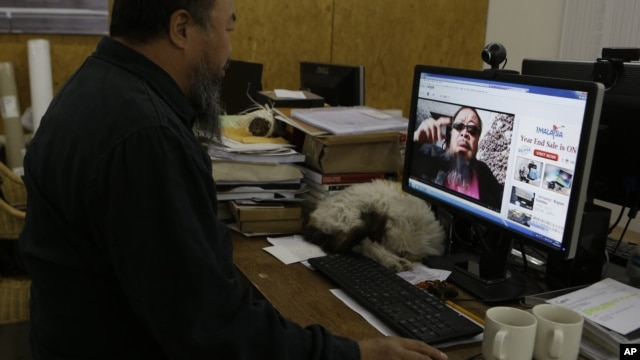 Chinese dissident artist Ai Weiwei plays a video clip he uploaded on Youtube on a computer in Beijing, China, October 25, 2012.