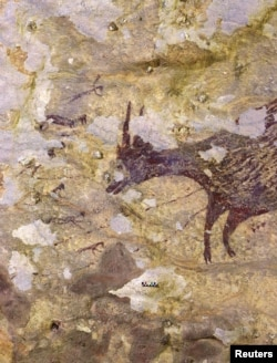 A cave painting dating back to nearly 44,000 years, according to a study using uranium-series analysis and was published in 'Nature' journal, is seen in Leang Bulu' Sipong 4 limestone cave in South Sulawesi, Indonesia.