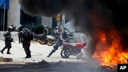 A Venezuelan Bolivarian National police officer drops a privately owned motorcycle into the flames after an explosion at Altamira square during clashes against anti-government demonstrators in Caracas, Venezuela, Sunday, July 30, 2017.