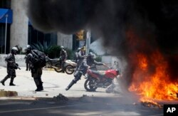 A Venezuelan Bolivarian National police officer drops a privately owned motorcycle into the flames after an explosion at Altamira square during clashes against anti-government demonstrators in Caracas, July 30, 2017.