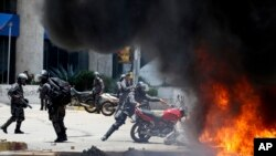A police officer drops a privately owned motorcycle into the flames of a fire resulting from an explosion, at Altamira Square during clashes with anti-government protesters, in Caracas, Venezuela, July 30, 2017.