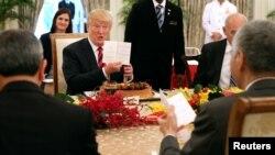 6·12 미북상회담을 하루 앞둔 11일 도널드 트럼프 미국 대통령이 싱가포르 이스타나궁에서 열린 리셴룽 싱가포르 총리와 확대정상회담 도중, 깜짝 생일 케이크를 받고 카드를 들어 보이고 있다.