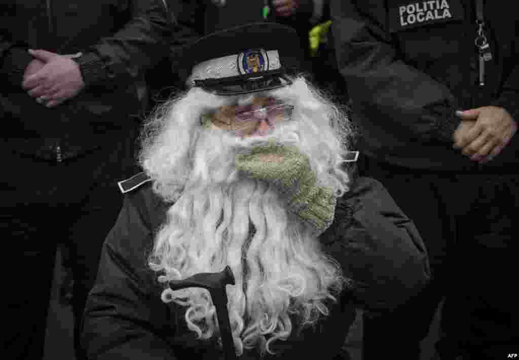 Buxarestdə etiraz aksiyası zamanı yerli polis özünü yaşlı işçiyə oxşatmaq üçün saxta saqqal taxıb. Rumıniya.