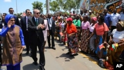 FILE - Turkey's President Recep Tayyip Erdogan and his wife, Emine Erdogan, greet local people during a ceremony in Maputo, Mozambique, Jan. 24, 2017.