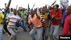 Striking miners dance and cheer after they were informed of a 22 percent wage increase offer outside Lonmin's Marikana mine, 100 km (60 miles) northwest of Johannesburg, September 18, 2012.
