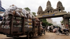Cambodian workers transport their goods from Thailand at a Cambodia-Thai international border gate in Poipet, Cambodia, Wednesday, June 18, 2014 for their daily work near the border between Cambodia and Thailand. (AP Photo/Heng Sinith)