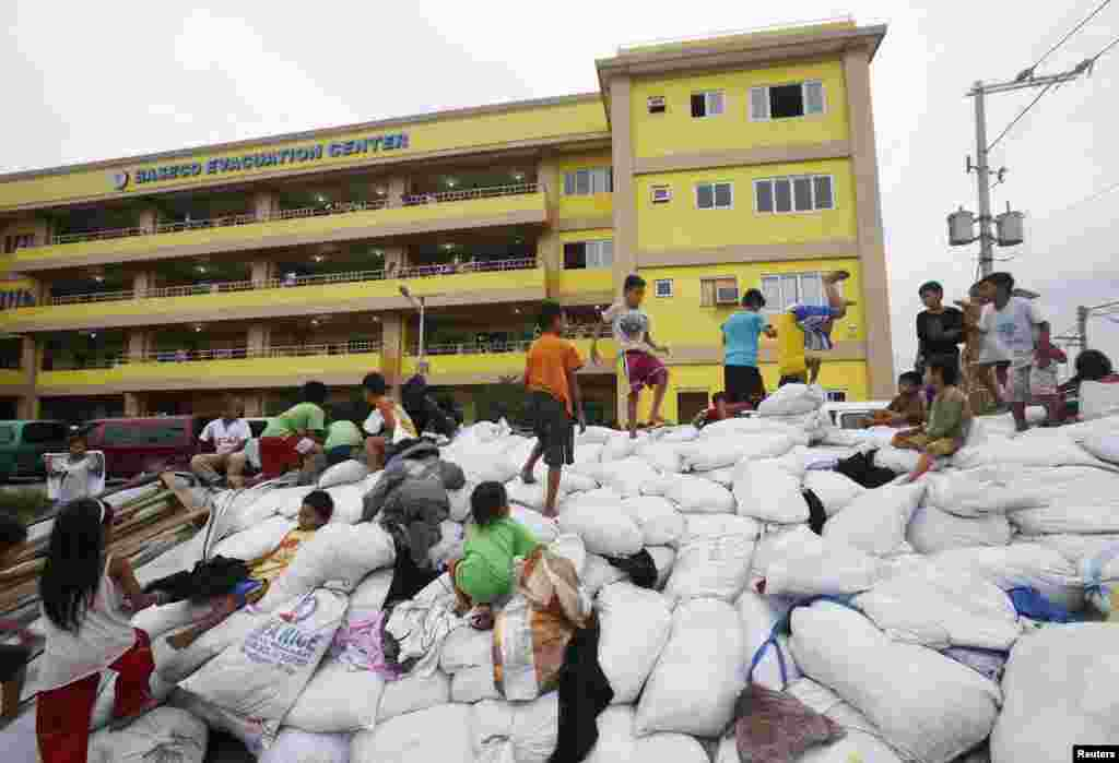 Children play atop sacks of donated clothes at an evacuation center for the coastal community to take shelter from Typhoon Hagupit in Manila, Dec. 8, 2014.