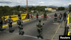Vệ binh quốc gia Venezuela (dưới) đứng trước mặt binh sĩ Colombia tại cầu quốc tế Simon Bolivar, ở San Antonio bang Tachira, Venezuela, 20/8/2015.