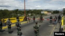 La Guardia Nacional de Venezuela front a soldados colombianos en el puente internacional Simon Bolivar.
